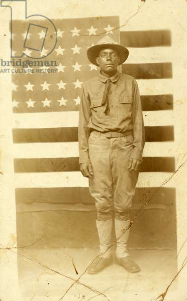 World War I soldier with American flag in background, 1914-18 (b/w photo)