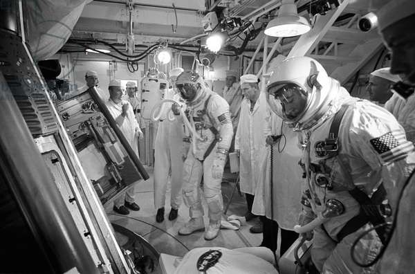 In the White Room atop the Gemini launch vehicle, astronauts Michael Collins (left), pilot, and John W. Young (right), command pilot, prepare to enter the Gemini-10 spacecraft, 18th July 1966 (b/w photo)
