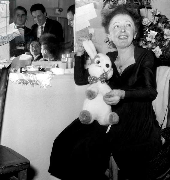 French Singer Edith Piaf Holding A Cuddly Toy Stuffed Rabbit in Dressing Room of Olympia Theatre December 30, 1960 (b/w photo)