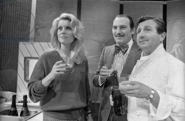"""French cook Michel Guerard (r) and actress Catherine Deneuve celebrating with Jean Ferniot (c) their nomination for the National Order of Merit during tvprogram """"Cuisine Legere"""", Paris, January 22, 1980 (b/w photo)"""