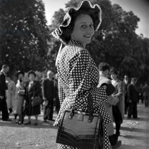Fashion in Longchamp, Paris, May 9, 1948 : Elegant Woman Wearing A Polka Dot Dress and A Hat (b/w photo)