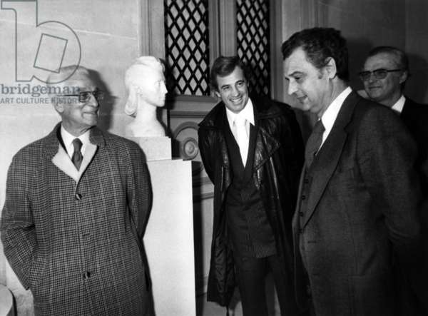 """Minister Delegate To Finance Michel Durafour In The Company Of Paul And Jean-Paul Belmondo During The Inauguration At The Musee De La Monnaie De Paris Quai Conti At The Exhibition """"Belmondo A La Monnaie"""" Paul Belmondo Y Presents Several Scultures Of Drawings Of Books Illustrations And Medals November 19, 1976 (b/w photo)"""