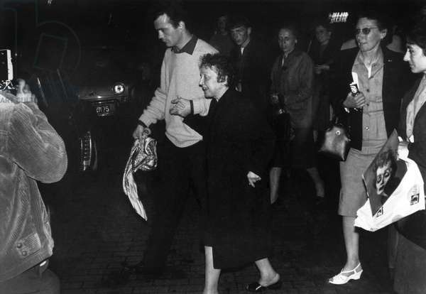 Edith Piaf, Very Escorted And Escorted By The Crowd After Her Singing Tour In Caen, Leaning On The Arm Of Her Secretary Claude Figus. June 21, 1962 (b/w photo)
