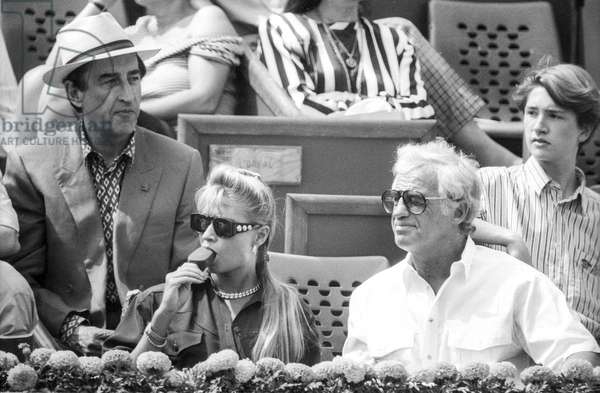French actor Jean Paul Belmondo attending Roland Garros tennis tournament with his girlfriend Natty (Nathalie Tardivel) on May 31, 1991 (b/w photo)