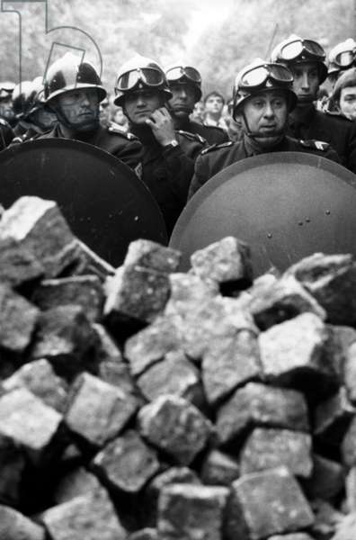 Members of the French riot police with helmet and shiled behing pile of cobblestones during demonstration in Paris on may 1968