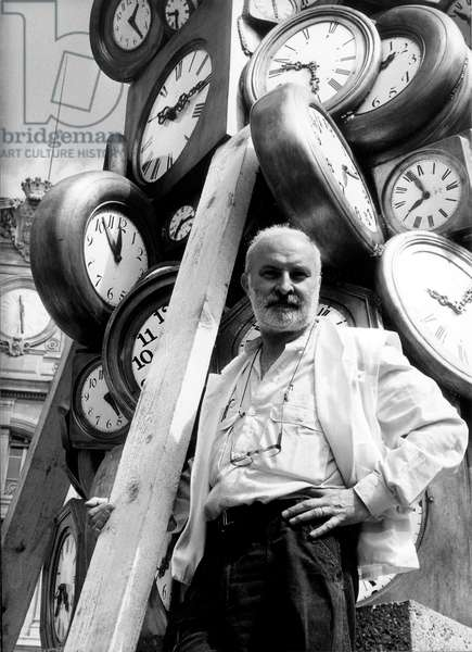 Sculptor Armand Fernandez Said Arman (1928-2005) here in Saint Lazare Station in Paris on July 22, 1985 in Front of One of his Sculptures (b/w photo)