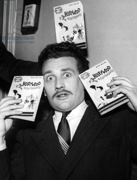 Writer Maurice Raphael With his Book 'Hollywood-Mediterranee', in A Bar Located Avenue De L'Opera, Paris, France, January 5, 1952 (b/w photo)