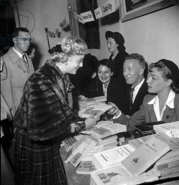 Sale by the CNA (Comite national des acteurs) on October 22, 1949 in Paris : Suzy Carrier and Simone Signoret (b/w photo)