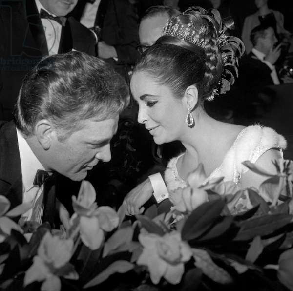 Richard Burton and Elizabeth Taylor during a party at the English Embassy in Paris after the opening night of 'Lawrence of Arabia', 15th March 1963 (b/w photo)