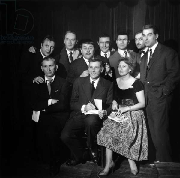 """On the Occasion of The Release Of Their Book """"Funny De Numbers"""": Jacqueline And Jean Diwo Had Convie A Cocktail Chez """"Milord L'Arsouille"""" G-D: Standing Raymond Devos, Francis Claude, Francis Blanche Jean Marc Thibault, Jacques Dufhilo, Michel Serrault, Jean Poiret; And Assis Maurice Henry Et Les Auteurs Jean Et Jacqueline Diwo Le 13 November 1958 Diwo Le 13, Jean Et. 938 (b/ w photo)"""