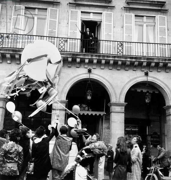 Salvador Dali at The Balcony of Bedroom at Hotel Meurice in Paris November 24, 1967, Looking at Balloons Flight on Saint Catherine Day (Holiday Made For Women Who Reach 25 Years of Age Without Marrying Which Symbolized Their Spinsterhood They Wore Unusual Hats To Show Their Status) (b/w photo)