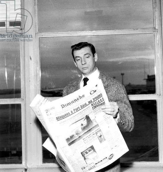 Yves Montand Reading Newspaper About Suez Crisis December 16, 1956 at Paris Orly Airport, Before Leaving For Moscow (b/w photo)