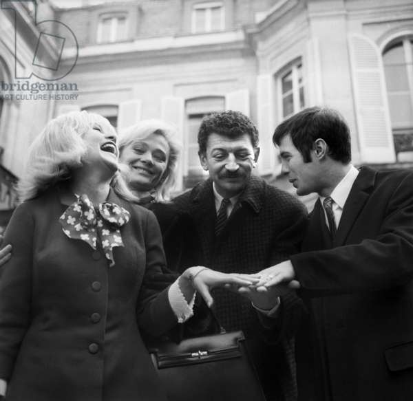 Guy Bedos & Sophie Daumier Show To Yves Robert and Daniele Delorme Their Wedding Rings in Coming Out of The 9Th Arrondissement'S Cityhall of Paris Where They Just Get Married on The 19Th February 1965 (b/w photo)