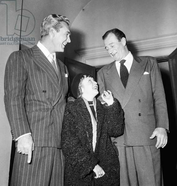 Reception given in honour of John Wayne, Paris, March 5, 1951 : Forest Picker, Josee Ariel and John Wayne (b/w photo)
