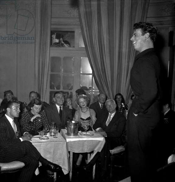 Yves Montand Singing in The Restaurant Cabaret Chez Carrere in Paris Under Look of Clark Gable and Mrs O'Brien, July 20, 1948 (b/w photo)