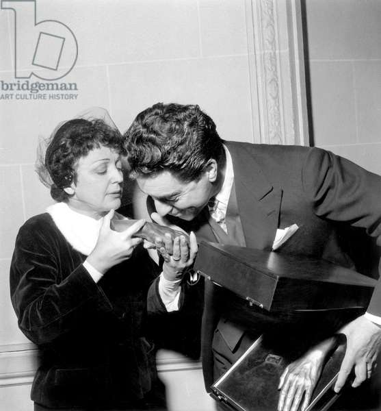 Edith Piaf and her Husband Jacques Pills Celebrating 1St Wedding Anniversary January 04, 1954 : Jacques Pills Is Kissing Bronze Casting of Hands of Piaf (b/w photo)