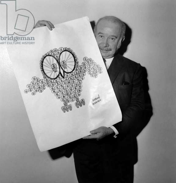 """Draftsman Herve Morvan, Member of the Jury of the """"Owls By Thousands"""" Contest wearing one of his drawings, before selecting the 100 Best Children's Drawings. October 10, 1969 (b/w photo)"""
