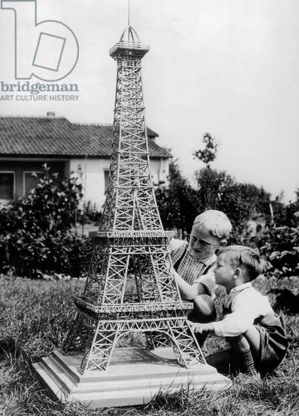 Children With An Eiffel Tower Made With Matches (Built By Manfred Thimm, Turist, When He Came Back From Paris) July 4, 1983 (b/w photo)