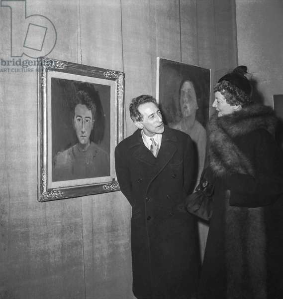 Exhibition of paintings by Christian Berard in Paris, February 22, 1950 : Jean Cocteau showing to Mrs Labisse his portrait by Berard (b/w photo)