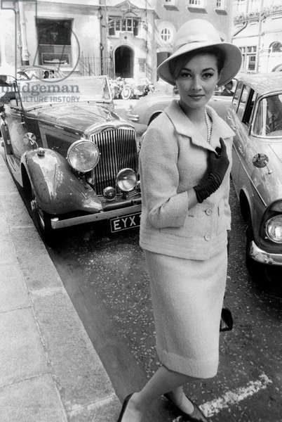 Actress Daniela Bianchi Wearing A Edward Mann Yellow Woman'S Suit and Cloche Hat and Posing in Front of Bentley Luxury Cars October 1963  (b/w photo)