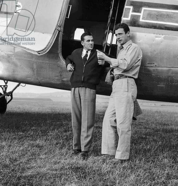 """Yves Montand and an Air France pilot at time of film """"Heroes and Sinners"""", July 6, 1955 at Cormeilles en Vexin airfield, France (b/w photo)"""