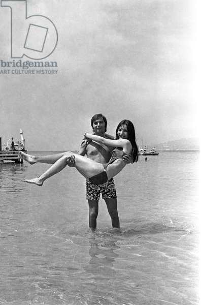 French Singer Pierre Vassiliu and Hungarian Singer Szabo on The Beach in Antibes, France, June 30, 1969 (b/w photo)