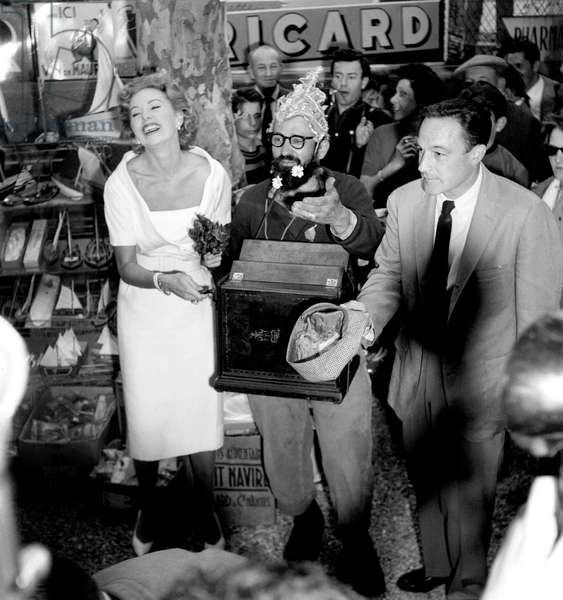Ronda Fleming Playing Barrel Organ With Aguigui and Gene Kelly Passing The Hat Round at Cannes Film Festival May 4, 1959 (b/w photo)