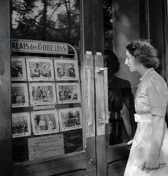 Young woman in front of the Palais des Gobelins (movie theatre) in Paris, August 1949 (b/w photo)