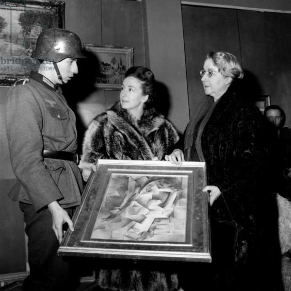 "Suzanne Flon on The Set of The Movie Called ""The Train"" That Tells The Story of A Paintings Theft By Germans in 1944. here With Madame Rose Valland As She Plays her Role , She Unpacks A Collection'S Painting With An Actor Who Plays A German Soldier in The Movie The 28Th December 1963 (b/w photo)"