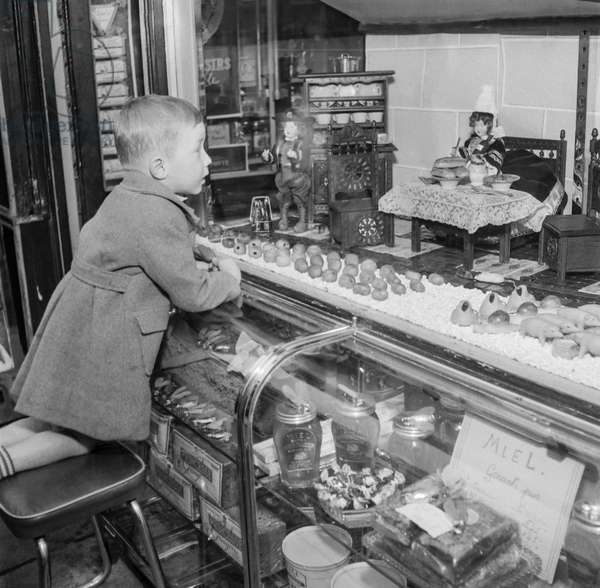 Exhibition about the pleasures of the food in Neuilly, France, October 17, 1950 : a boy looking at biscuits and cakes (b/w photo)
