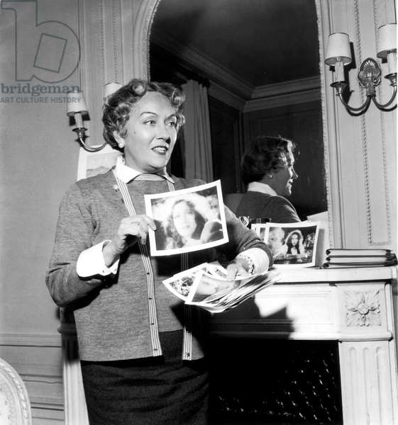Gloria Swanson (1899-1983) montrant des photos de elle-même C ; 1950 (photo de B/w)