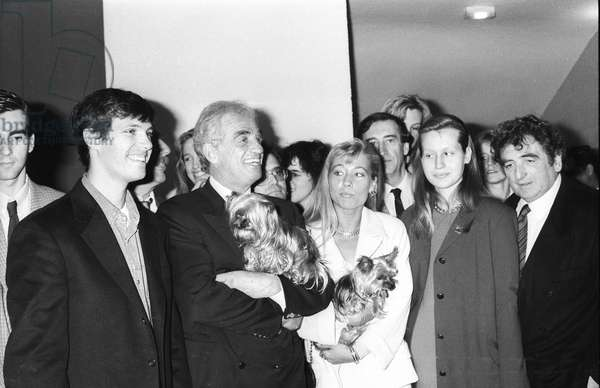 French racing driver Paul Belmondo with his father French actor Jean Paul Belmondo and the latter's girlfriend Natty (Nathalie Tardivel) with their Yorshire terrier dogs at the display of Voiture3000 in Paris on April 8, 1991 (