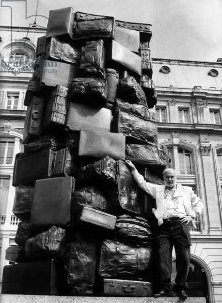 French Sculptor Armand Fernandez Aka Arman (1928-2005) Outside St Lazare Station in Paris Near his Work of Art (Cases and Bags), July 22, 1982 (b/w photo)