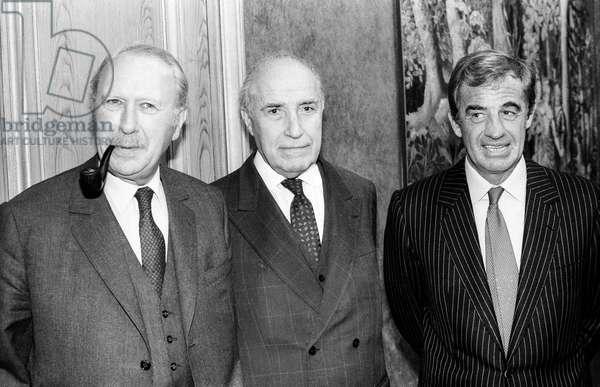 French novelist Jean Dutourd, Edouard Bonnefois and French actor Jean Paul Belmondo after having given sculptor MauroCorda the PaulBelmondo award on December 5, 1985 (b/w photo)