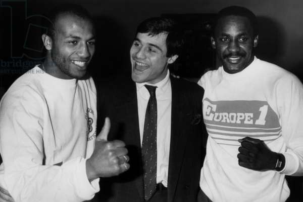 Left French Boxer Freddy Skouma And Right American Boxer Mccallum (World Champion Wba Super Welters During A Common Press Conference At A Grand Parisian Hotel With At The Centre Louis Acaries Match Organizer On October 20, 1986 (b/w photo)