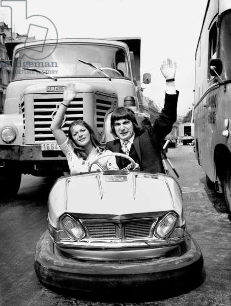 Anne Marie Peysson and Serge Lama Driving Bumper Car in Saint Germain Des Pres in Paris To Announce Fun Fair July 06, 1970 (b/w photo)