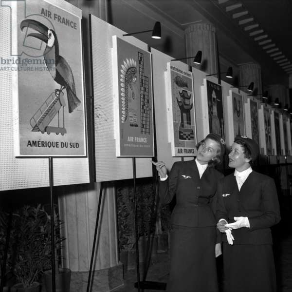 Stewardess Looking at Air France Posters, May 17, 1956 (b/w photo)
