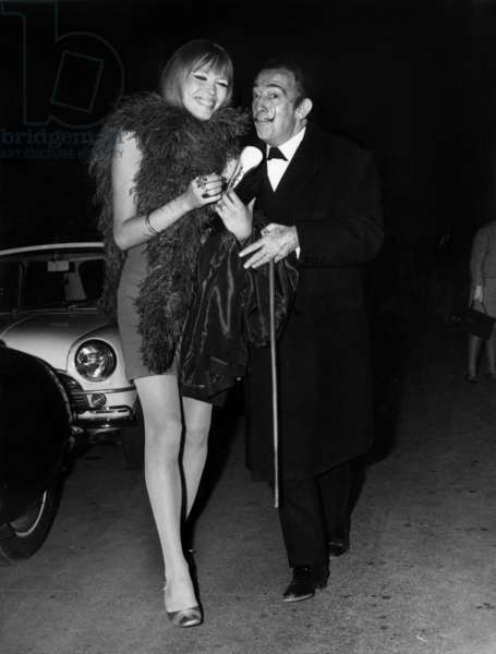 "Spanish Pintor Salvador Dali With French Singer and Presenter Amanda Lear, Arriving To The Gala ""La Nuit Des Generaux"" (Generals Night), April 20, 1970 (b/w photo)"