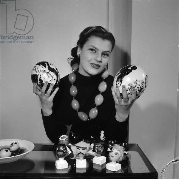 Woman holding two painted eggs by Chagall and Erni. (Photography) 1952
