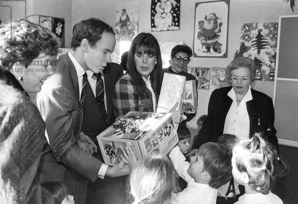 Christmas of the Red Cross in Monaco, December 21, 1988 : Prince Albert of Monaco (futur Albert II) and Princess Caroline giving presents (b/w photo)