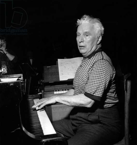 Charlie Chaplin Playing The Piano on June 24, 1957 (b/w photo)