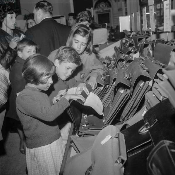 Start of the school year : children looking for a school bag, Paris, September 1st, 1960 (b/w photo)
