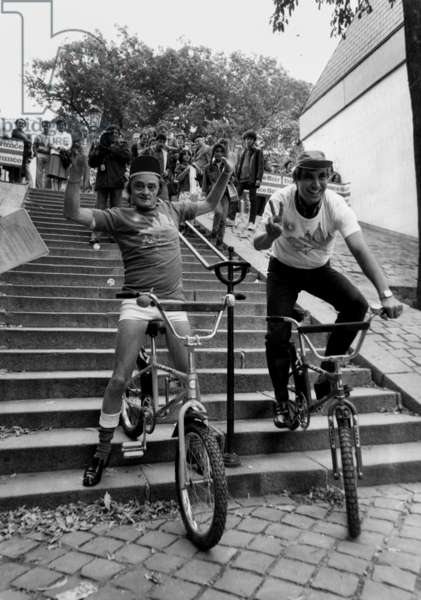 Sim et Jean-Pierre Foucault Chevauchant dans les escaliers à Montmartre, Paris, le 23 septembre 1982 (photo b/s)