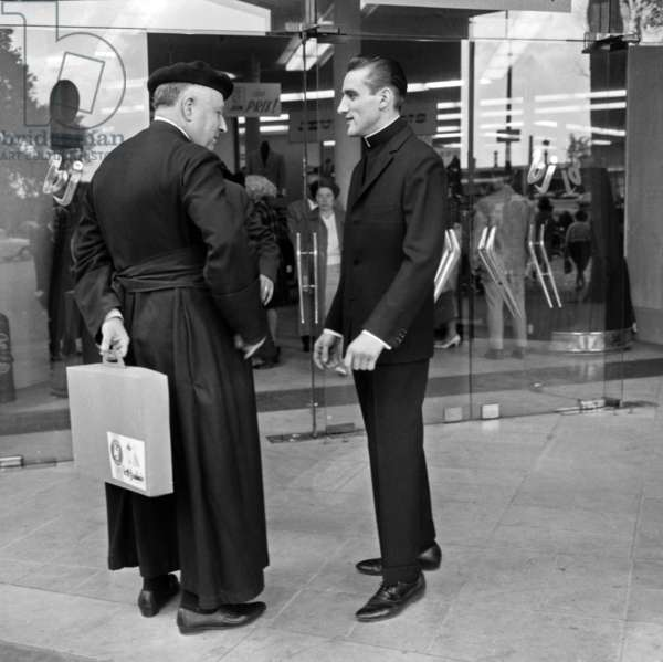 """The Parisian Clergyman Will Be Permission To Wear Black or Dark Grey Clergyman Dress With The Roman Collar As Distinguishing Sign According to The Communiqué Of The """"Religious Week"""" Sign Of Cardinalfeltin. Here is a """"Model"""" from a department store specialises in posing with this new suit, an Abbe with the traditional cassock is trove face to face with this new outfit that he will be able to adopt instead of the Cassock. June 28, 1962. Neg 1346118 (b/w photo)"""