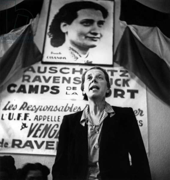 "A Woman of The Association ""Union of The French Women"" Presentes A Speech Infront of The Portrait of Danielle Casanova (French Resistant Who Died in Auschwitz) in Order To Welcome The Prisoners of The Concentration and Extermination Camp of Ravensbruck and Auschwitz C.May 1945 (b/w photo)"