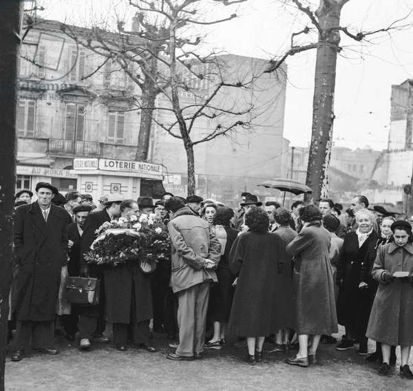Trial of Oradour-sur-Glane at Bordeaux military court on February 1st, 1953 : people from Oradour putting flowers at the war memorial in Bordeaux (b/w photo)