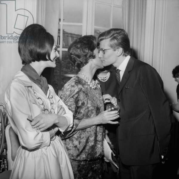 Presentation of Dior Collection (Autumn-Winter 1960-1961) in Paris on July 27, 1960 : L-R : Model Kouka, Lucienne Mathieu Saint-Laurent Kissing her Son Yves Saint-Laurent (b/w photo)