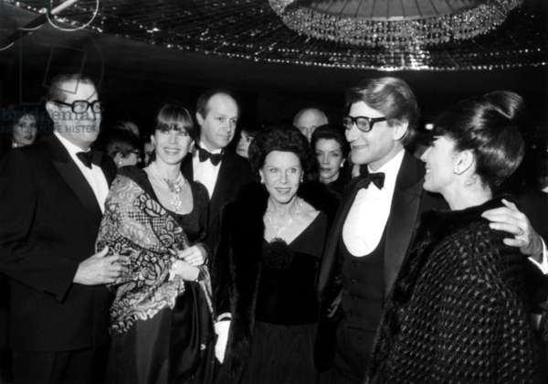 Party To Celebrate 20 Years of Haute Couture of Yves Saint Laurent at The Lido in Paris on January 29, 1982 : on L With Glasses Charles, Father of Ysl, on R : Yves Saint-Laurent With his Mother Lucienne (Fur and Necklace) and Model Victoire (Victoire Doutreleau) (b/w photo)