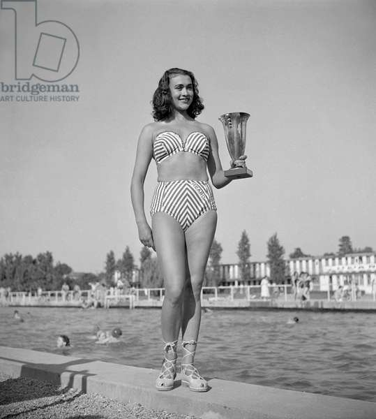 Contest of the most beautiful female bather (young women wearing bathing suit), Paris, June 19, 1949 : Renee Cousture, 22, with a bikini and her cup (b/w photo)