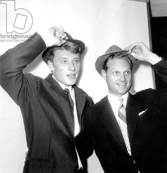 Singer Johnny Hallyday With his Cousin By -Marriage Lee Ketcham Presenting New Tyrolean Model Hat September 27, 1961 during Cocktail For French Elegance (b/w photo)